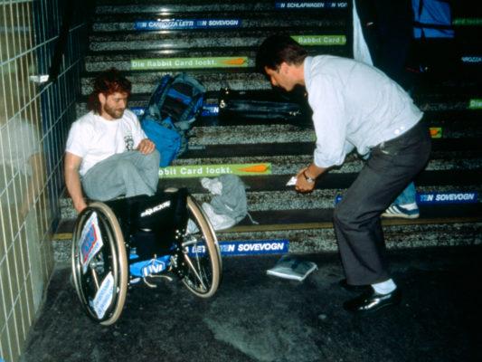 [1990] Paris? Usikkert sted. Hebbe har mistet rullestolen ned trappa og det ligger en del ting omkring ham og rullestolen. En mann hjelper til.