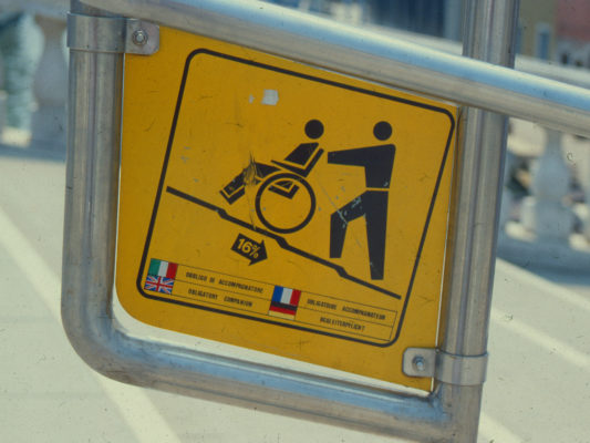 [1990] Venezia: Skilt som viser at trappen har 16% helling og at det er obligatorisk med ledsager. Tekst på 4 språk.
