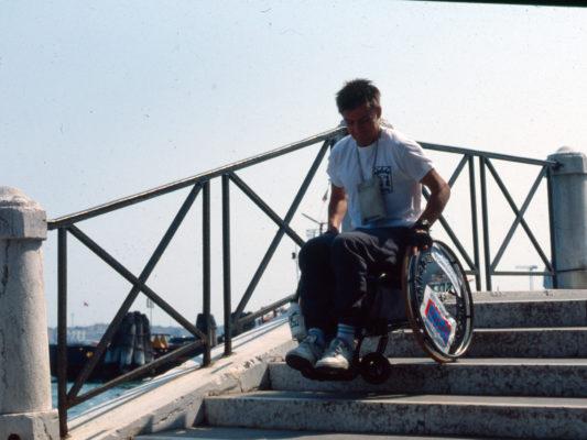[1990] Leif på veg ned trapp i rullestol. Det ser ut som rullestolen er i ferd med å tippe framover.