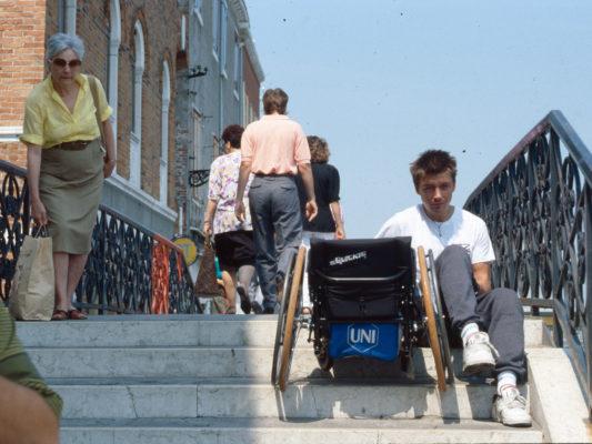 [1990] Venezia: Leif på veg opp trapp. Sitter på nest øverste trinn, trekker rullestolen etter seg. Ser tydelig sliten ut.