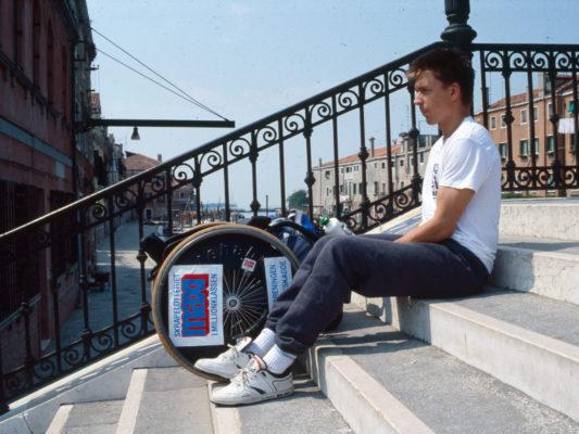 [1990] Venezia: Leif trekker rullestolen opp trappa. BIlde tatt fra siden.