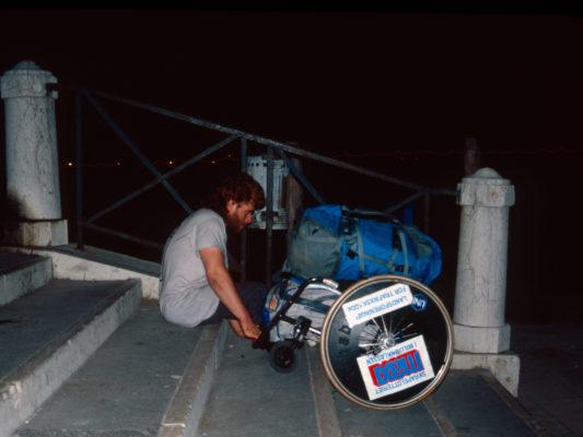 [1990] Venezia. Hebbe sitter i trapp og trekker rullestolen etter seg. Under setet på rullestolen er det en bag, og oppå rullestolen ligger en full ryggsekk. Det er mørkt.