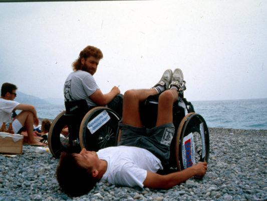[1990] Nice: Hebbe og Leif på stranda i Nice. Hebbe sitter i rullestol med røyk i hånda, Leif har tippet rullestolen bakover og ligger på ryggen.