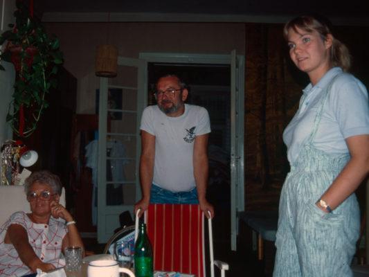 [1990] President, Handikapforbundet Budapest, Rosa Mach sitter og smiler, mannen står og smiler, datter ser litt overrasket ut. De har nettopp blitt fortalt at Leif ikke er funksjonshemmet.