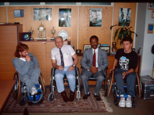 [1990] Hebbe og Leif sittende i rullestol sammen med to representanter for FN i Wien.