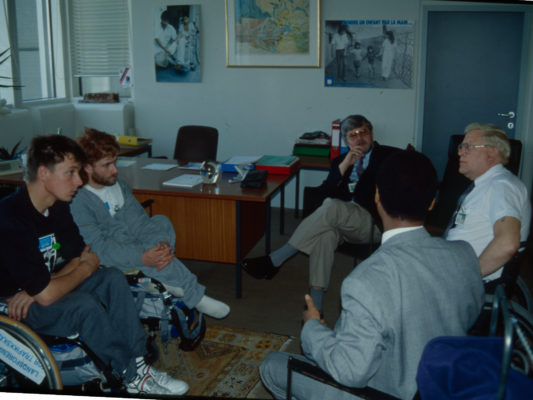 [1990] Hebbe og Leif sittende i rullestol prater med to representanter for FN i Wien og Norsk ambassadør.
