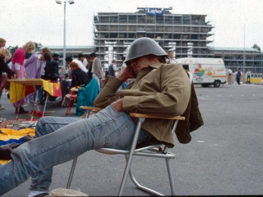 [1990] Scene fra torget ved Brandenburger Tor. Selger av militæreffekter sitter og sover i campingstol, med hjelm trukket ned foran øynene.