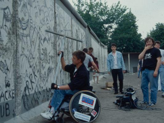 """[1990] Leif, sittende i rullestol, hakker løs på Berlinmuren med en stor metall """"T"""".."""