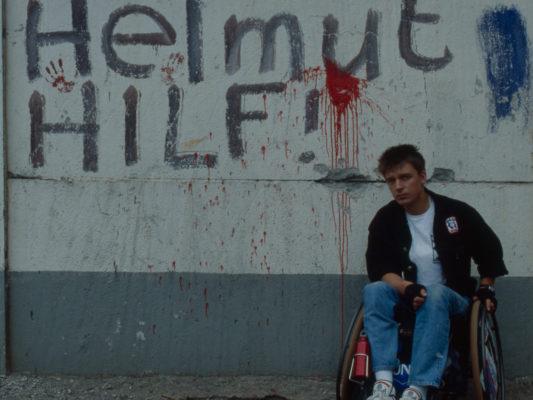 """[1990] Leif i rullestol foran Berlinmuren. Det står """"Helmut Hilf"""" på muren, rød maling er sprutet på veggen , og det er røde merker av hender."""