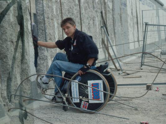 [1990] Leif i rullestol ved et hull i Berlinmuren. Mye bøyd armeringsjern omkring. Tydelig at muren er i ferd med plukkes fra hverandre.