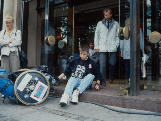 [1990] Leif sitter på trinn som fører inn til hovedinngangen til kjøpesenter. Trekker rullestolen etter seg.