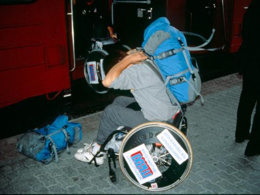 Leif i rullestol, trekker ryggsekk opp over ryggen, gjør klar for å entre tog. Hebbe skimtes i inngangen til toget i bakgrunnen.